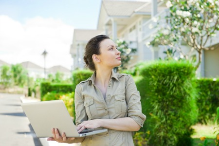 Female real estate agent with laptop outside homes