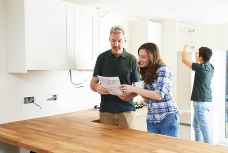 Couple looking at kitchen upgrades for new home
