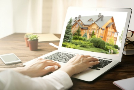 woman's hands on laptop keyboard with a home search on screen