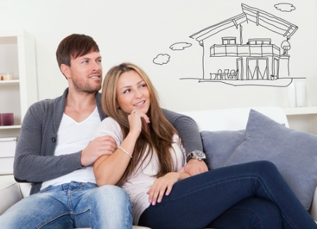 man and woman sitting on sofa and day dreaming about house to buy