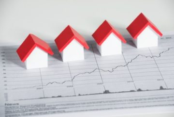 real estate market report concept of graph with small houses sitting on top