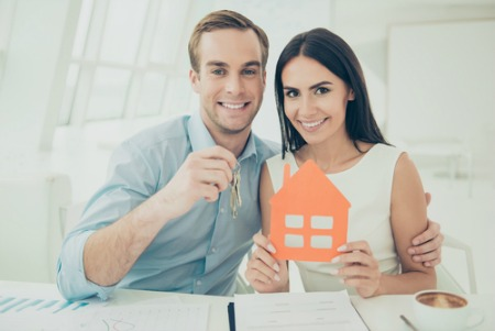 smiling man and woman holding keys and house cut out